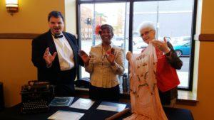 Joe Landmichl talks up an exhibit with two of his volunteers